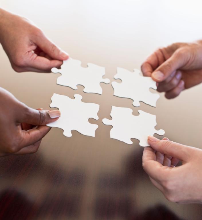 4 mani che tengono una tessera del puzzle
